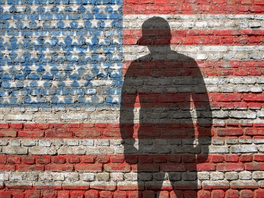 silhouette of man with cap against an American flag on a brick wall