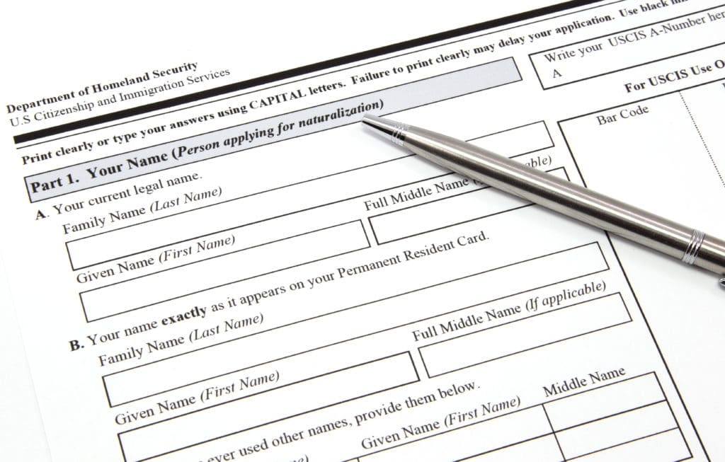 A U.S. citizenship and immigration application with a pen ready to be completed.
