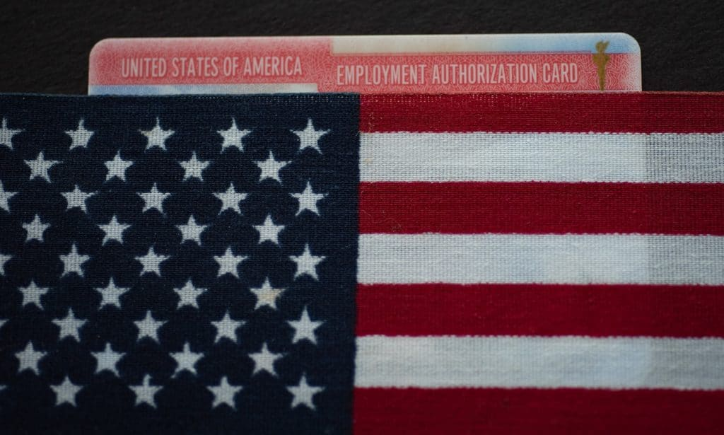 employment authorization card, or work permit, file with the American flag on top of it.