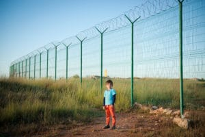 one little boy refugee in empty desert field near long fencing with barbed wire