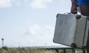 Refugee girl standing with her old suitcase on the countryside.