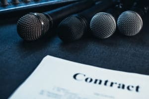 Microphones next to contract to be signed by both the producer and music artist.